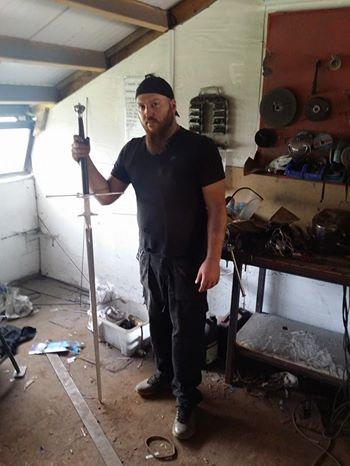 Марко Данелли в своей мастерской с двуручным мечом в руке.
